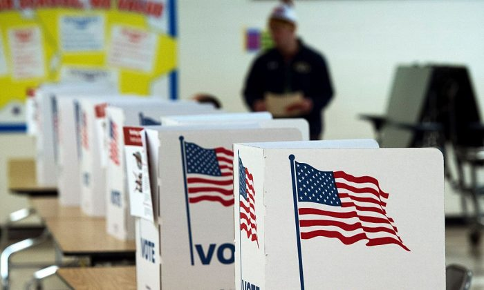 A man walks to use a voting booth 700x420